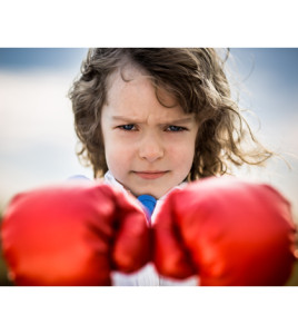 Kid wearing red boxing gloves. Girl power and feminism concept